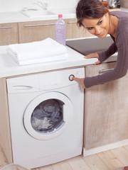 female pressing button on washing machine