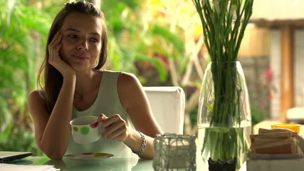 Relaxed  businesswoman drinking tea behind table at home