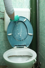Person wearing a turquoise rubber glove cleaning toilet