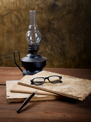 Still-life with old writing-books and an oil lamp