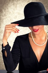 Attractive woman wearing black dress, hat and pearls
