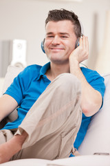 relaxed man listening to music in earphones
