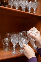 Female hands clean a crystal glass