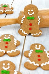 Christmas gingerbread men with rolling pin on white wood