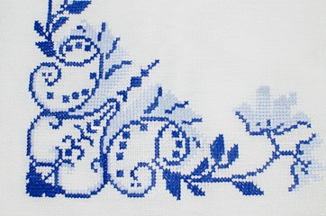 Cross stitch floral pattern on white canvas