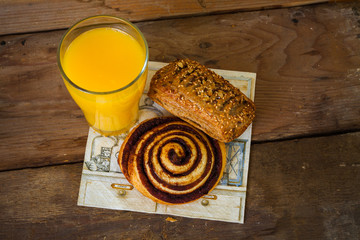 Snail and bun with orange juice on wooden background. Top view.