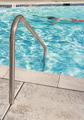 One swimming pool safety handrail with man swimming