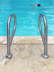Pair of swimming pool safety handrails with man swimming