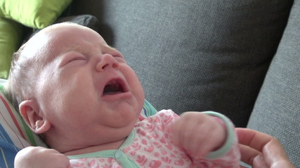 newborn crying on mom legs