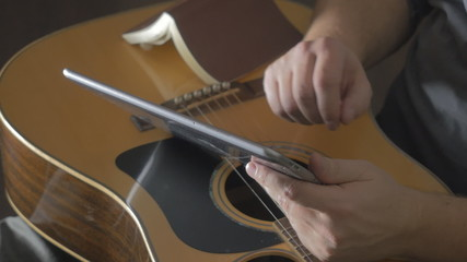 Man on sofa playing the guitar with tablet at home
