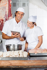 Butcher Using Digital Tablet With Female Colleague
