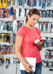 Woman Examining Product In Hardware Store