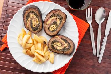 Arrosto farcito con spinaci a fette con patate fritte