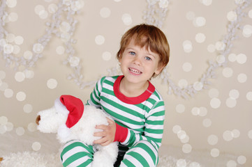 Winter Holidays: Laughing Happy Child in Christmas Pajamas Sled