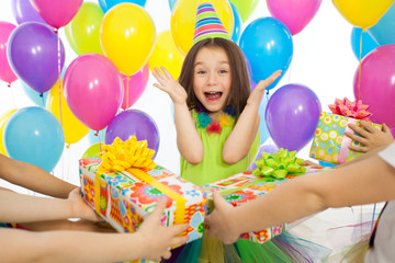 Joyful little kid girl receiving gifts at birthday party