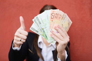 Business woman holding a fan of fifty and hundred-euro notes