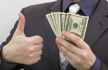 Man holding a hundred dollar banknotes