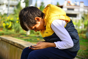 Boy playing with smart phone in the park