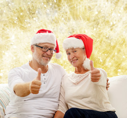 happy senior couple in santa helper hats