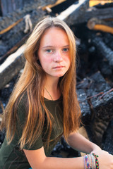 Young girl near the coals from the conflagration.