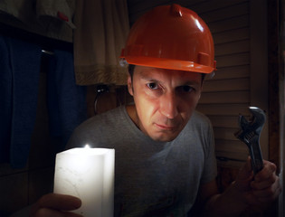 The plumber in a helmet with a nut key in the dark room.