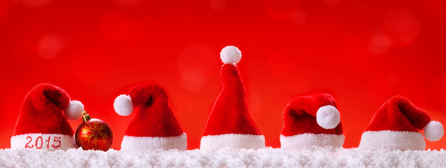 New Year 2015  red background with Christmas hats.