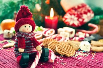 Close-up christmas wooden doll with sweets.