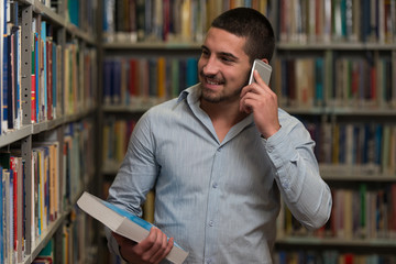 Handsome College Student Using Mobile Phone In Library