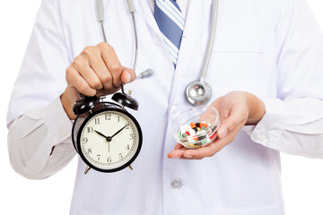 Asian male doctor show a clock and pills