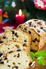 Sliced fruitcake with raisins and mint leaf on christmas backgro