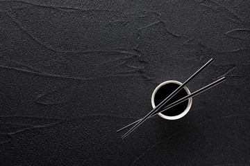 Chopsticks and bowl with soy sauce on black rock