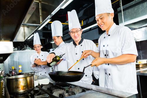 Asian Chefs in restaurant kitchen cooking - 73441023
