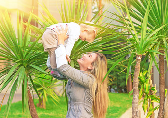 Cheerful mother playing with baby