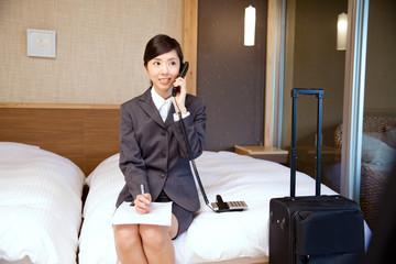 ベッドの上で電話で話すビジネスウーマン