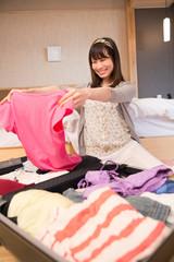 旅行の荷物のパッキングをする若い女性