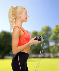 smiling sporty woman with skipping rope