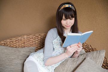 ソファで本を読む若い女性