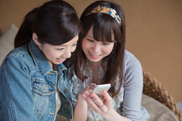 スマホを一緒に見る若い女性2人