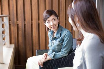 ソファに座って話す若い女性2人