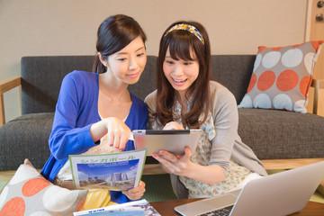旅行の計画をする若い女性2人