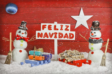 Two snowmen with a Merry Christmas signpost, words on spanish