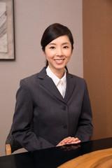 ホテルのフロントに立つ若い女性従業員