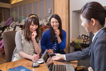 フロントで話すホテル従業員と女性客2人