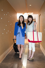 ホテルの廊下を歩く若い女性2人