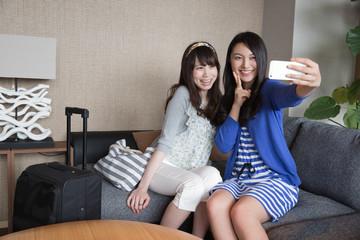 ホテルの客室でスマホで撮影する女性2人