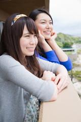 ホテルのベランダで景色を眺める女性2人