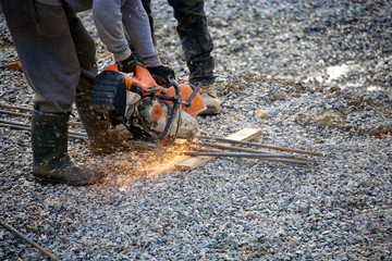 Close up of rebar being cut at a construction site.