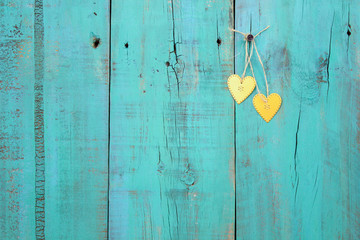 Gold metal hearts hanging on antique blue wooden background
