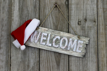 Wood welcome sign with Christmas Santa Claus hat
