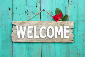 Welcome sign with flower hanging on antique wood background